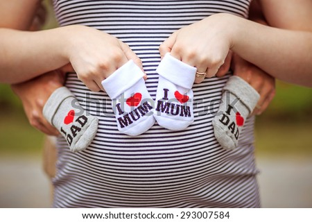Parents. Happy young couple in anticipation of the baby. Baby socks with I love mom and I love dad written on them - stock photo