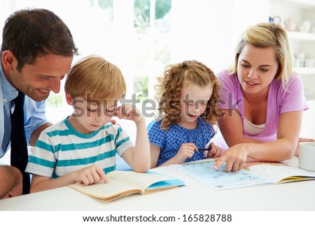 Parents Helping Children With Homework In Kitchen - stock photo