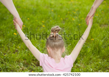 Parents holding daughter's hands, green natural background - stock photo