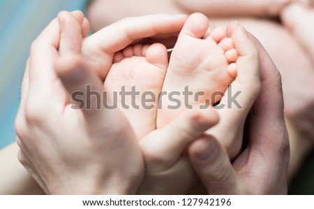 Parents  holding with love little newborns feets