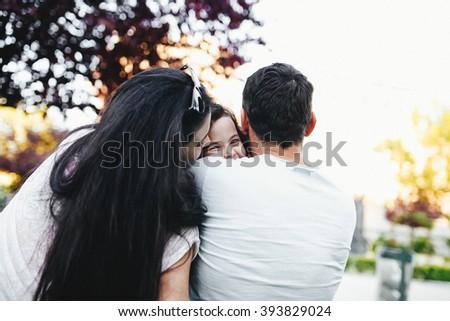 parents hug their beloved daughter - stock photo