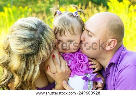 Parents kissing baby's cheek nature - stock photo