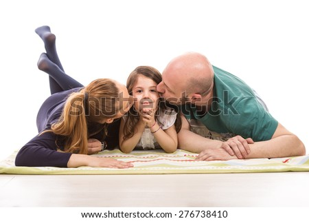 Parents laying on blanket in a row and kissing their daughter - stock photo