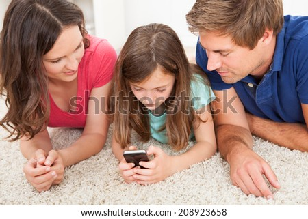 Parents looking at daughter using smart phone while lying on rug - stock photo