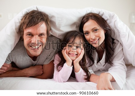 Parents lying under a duvet with their daughter in their bedroom - stock photo