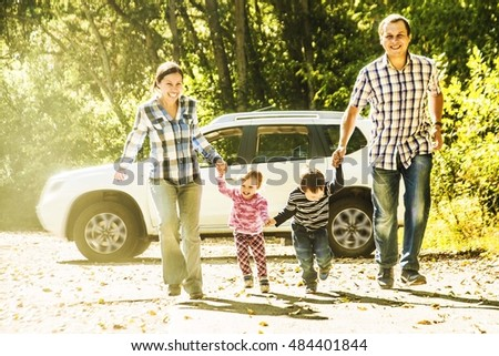 Parents - mother, father and kids - daughter, son holding hands each other against white SUV big car. Outdoor photo in summer park. Casual dress. Sunset light rays.