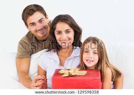 Parents offering a gift to their daughter on a sofa