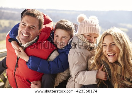 Parents piggy back kids in the countryside, looking away - stock photo