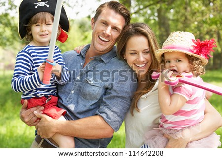 Parents Playing Exciting Adventure Game With Children In Summer Field - stock photo