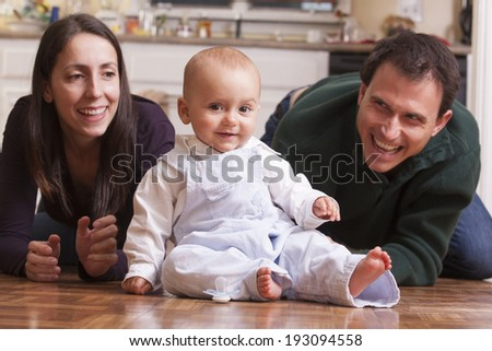 Parents playing on the floor with their son  - stock photo