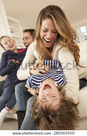 Parents playing with children at home - stock photo