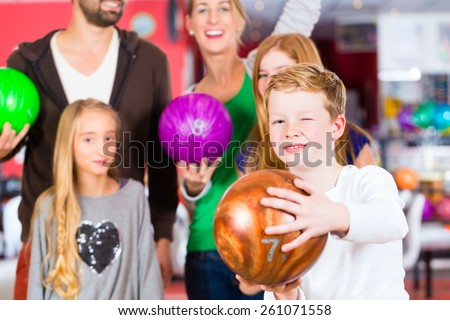 Parents playing with children together at bowling center - stock photo