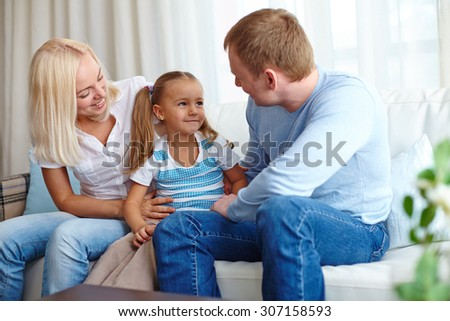 Parents playing with their daughter