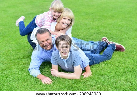 Parents playing with their kids in garden - stock photo
