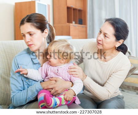 Parents problems. Mature woman comforting adult daughter with baby - stock photo