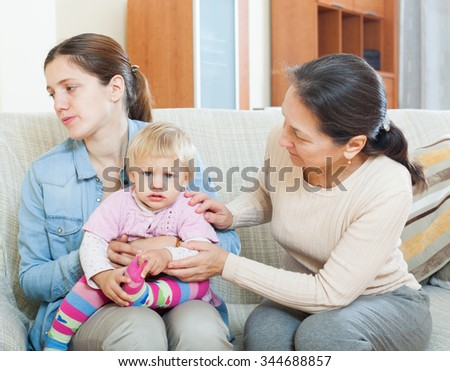 Parents problems. Mature woman comforting adult daughter with baby in living room at home