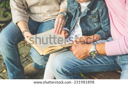 parents reading a story on a book to their daughter. concept about family - stock photo