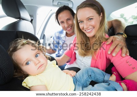Parents securing baby in the car seat in their car - stock photo