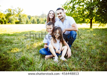 Parents Sitting With Children In Field Of Summer Flowers.Happy family having weekend in summer park