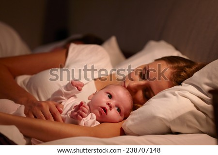 Parents Sleeping In Bed With Newborn Baby - stock photo