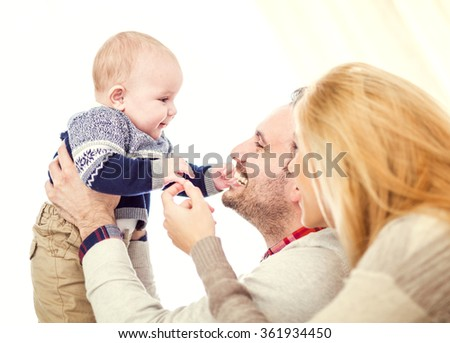 Parents spending quality time with their baby.A happy couple holding their beautiful baby and smiling.They are enjoying together and having a great time. - stock photo