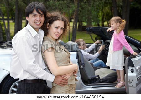 Parents stand near cabriolet embraced slightly, children play in the car