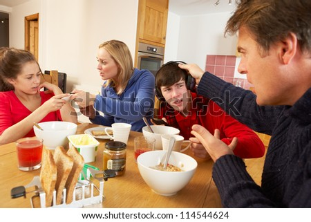 Parents Taking Away Gadgets From Children Whilst Eating Breakfast Together In Kitchen - stock photo