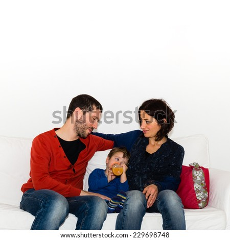 Parents taking care of the child giving him the bottle on the couch and smiling together - stock photo
