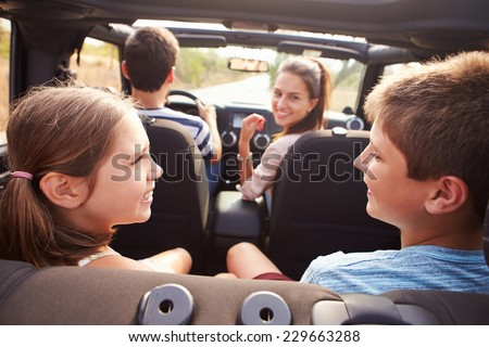 Parents Taking Children On Trip In Open Top Car - stock photo