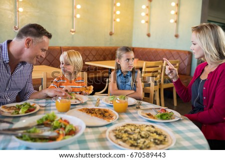 Parents talking to children at table in restaurant