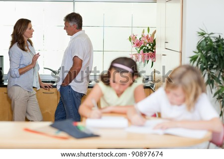 Parents talking with their children doing homework in front of them - stock photo