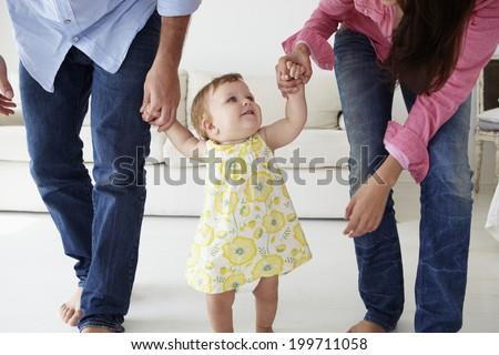 Parents teaching baby girl to walk - stock photo