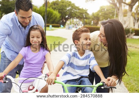Parents Teaching Children To Ride Bikes In Park - stock photo