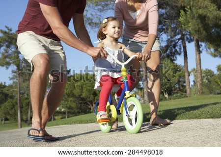Parents Teaching Daughter To Ride Bike In Park - stock photo