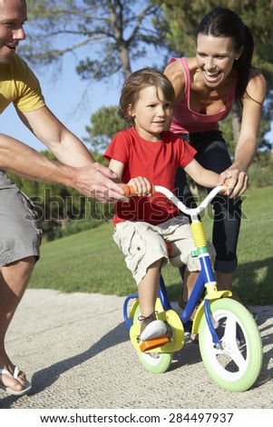 Parents Teaching Son To Ride Bike In Park