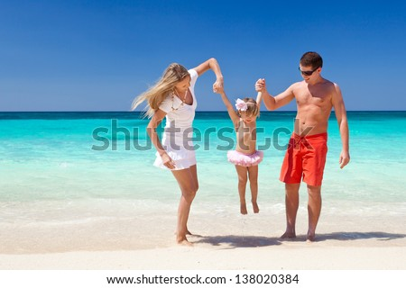 Parents throwing their daughter in air at the tropical beach - stock photo