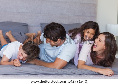 Parents tickling their children on bed at home - stock photo