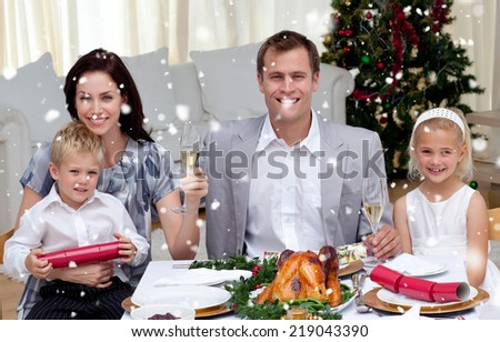 Parents toasting with champagne in Christmas dinner against snow falling - stock photo