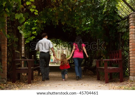 Parents together with daughter enter into tunnel from an ivy in summer garden. - stock photo