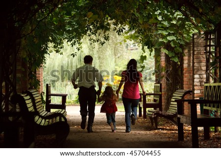 Parents together with daughter escape on tunnel from ivy in summer garden. - stock photo