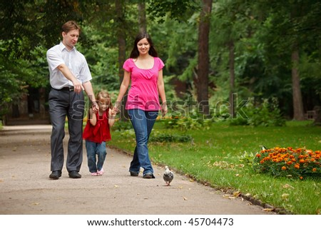Parents together with daughter walk on summer garden. Man shows to girl of pigeon. - stock photo