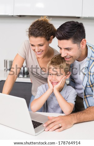 Parents using laptop with their son at home in kitchen - stock photo