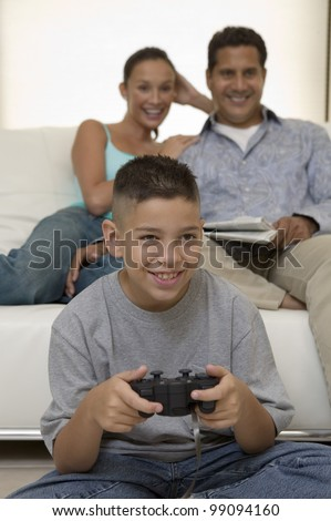 Parents Watching Son Play Video Games - stock photo