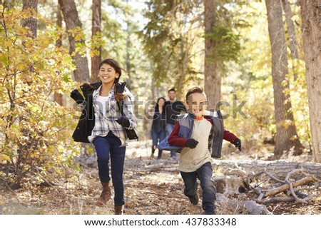Parents watching their children running in a forest - stock photo