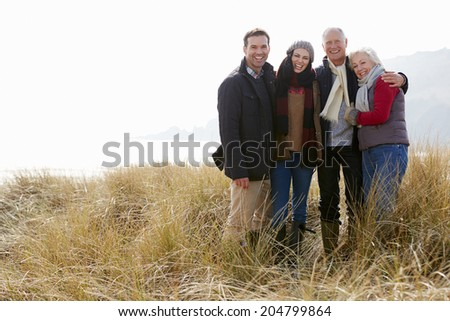 Parents With Adult Offspring Standing In Dunes - stock photo