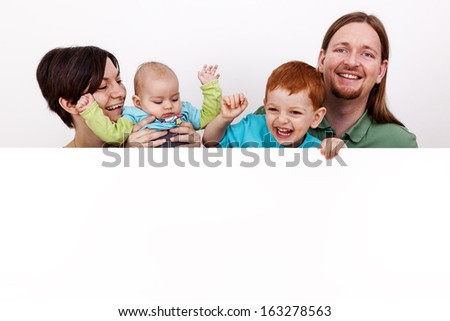 Parents with baby and child behind white wall