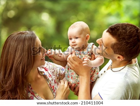 parents with baby in park - stock photo