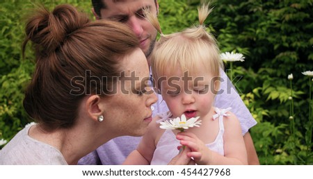 parents with baby smelling flowers, smiling and laughing - stock photo
