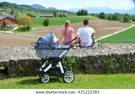 Parents with baby stroller enjoing Alpine panorama. Switzerland