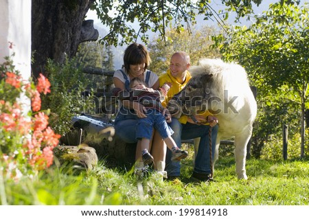Parents with child sitting in garden, playing with pony